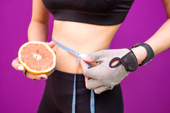 Slim young woman measuring her thin waist with a tape measure and with grapefruit Royalty Free Stock Image