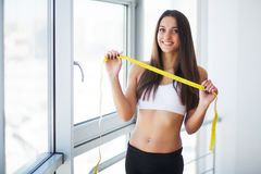 Slim young woman measuring her thin waist with a tape measure stock photos