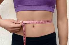 Slim young woman measuring her waistline. Athletic young woman measuring her waistline with  centimeter type. Fitness body Stock Photography