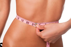 Slim young woman measuring waist Royalty Free Stock Photography