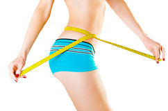 Slim young woman measuring waist. On a white background Royalty Free Stock Image