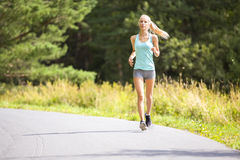 Slim young woman running on a road in the forest Stock Photos