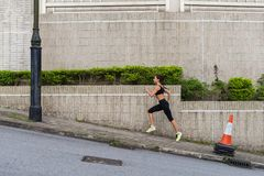 Slim young woman running uphill on sidewalk of city street. Female athlete training outside royalty free stock image