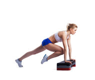 Slim young woman with stepper Royalty Free Stock Photos