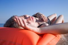 Slim young woman in swimsuit sunbathes on pink pool raft. Girl in swimwear lying on back on beach with eyes closed Stock Photography