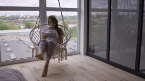 Slim young woman swinging in a hanging chair while using her tablet at the large floor-to-ceiling window. Freelance stock video