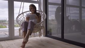 Slim cute young woman swinging in a hanging chair while using her tablet at the large floor-to-ceiling window. Freelance stock footage
