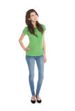 Slim young woman wearing green shirt and blue jeans in full body. Length looking happy and satisfied up to the text Stock Photos