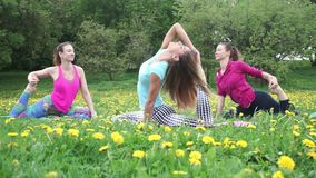 Slim and young women sit in twine position and stretch legs. Slim young women sit in twine position and stretch legs at workout on warm spring day among stock video