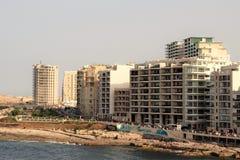 Slima, Malta, Lipiec 2014 Nowożytni budynki na nabrzeżu plaży i ludziach odpoczywać, obraz stock