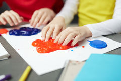 Slime creativity. Contemporary schoolkids playing with multi-color slime stock photography