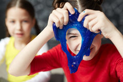 Slime peeking. Happy kid looking through hole in blue slime stock photography
