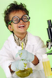 Slimey Delight. An adorable preschooler with wild hair and coke-bottle glasses delightedly stirring a bowl filled with yucky green slime Stock Photos