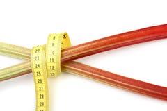 Slimline rhubarb. Tape measure wrapped around 2 sticks of rhubarb crossed on white background with slight shadow Stock Photo