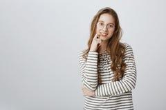 Slimme aantrekkelijke vrouw die met eerlijk haar in gestreept sweatshirt en transparante glazen, vinger houden ruim glimlachen di royalty-vrije stock afbeeldingen