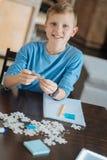 Slimme aardige jongen die raadselstukken samenbrengen Royalty-vrije Stock Foto