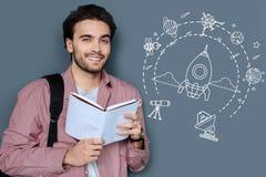 Slimme ambitieuze student die terwijl het dromen over het onderzoeken van de ruimte glimlachen Stock Afbeelding