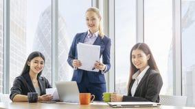 Slimme bedrijfsvrouwen die op kantoor met façade glassing achtergrond en de moderne bouw samenkomen concept van het groepswerk h stock foto's