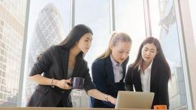 Slimme bedrijfsvrouwen die op kantoor met façade glassing achtergrond en de moderne bouw samenkomen concept van het groepswerk h royalty-vrije stock foto's