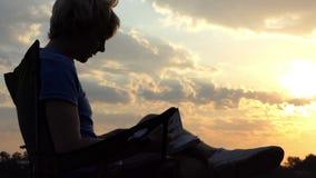 Slimme Blogger zit op een Vouwende Stoel en bekijkt Zijn Tablet zonsondergang stock footage