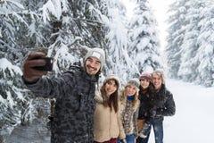 Slimme de Telefooncamera die van de mensengreep Selfie-de Glimlachsneeuw Forest Young People Group Outdoor nemen van Fotovrienden Royalty-vrije Stock Foto