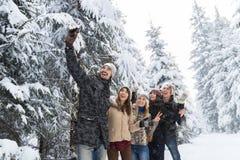 Slimme de Telefooncamera die van de mensengreep Selfie-de Glimlachsneeuw Forest Young People Group Outdoor nemen van Fotovrienden Royalty-vrije Stock Fotografie