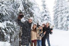 Slimme de Telefooncamera die van de mensengreep Selfie-de Glimlachsneeuw Forest Young People Group Outdoor nemen van Fotovrienden Stock Foto