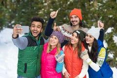 Slimme de Telefooncamera die van de mensengreep Selfie-de Winter van Forest Young People Group Outdoor van de Fotosneeuw nemen Royalty-vrije Stock Foto's