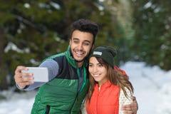 Slimme de Telefooncamera die van de mensengreep Selfie-Fotosneeuw Forest Young Mix Race Couple nemen de Openluchtwinter Royalty-vrije Stock Foto's