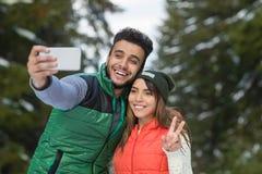 Slimme de Telefooncamera die van de mensengreep Selfie-Fotosneeuw Forest Young Mix Race Couple nemen de Openluchtwinter Royalty-vrije Stock Afbeelding