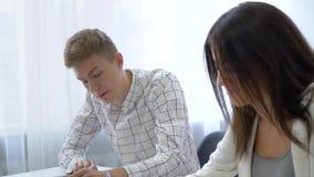 Slimme glimlachende mannelijke en vrouwelijke studenten die de vragen van de leraar in licht klaslokaal in dag beantwoorden stock videobeelden