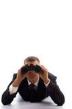 Slimme jonge advocaat die een paar verrekijkers gebruikt Stock Fotografie