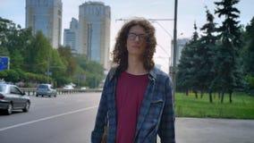 Slimme jonge mens die in glazen met lang krullend haar op taxi en wat betreft zijn haar wachten, die zich op bushalte dichtbij we stock videobeelden