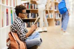 Slimme jongen die interessant boek lezen stock afbeelding