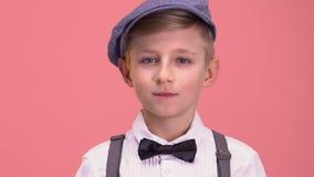 Slimme jongen die in die retro kleren camera onderzoeken, op roze achtergrond wordt geïsoleerd stock video