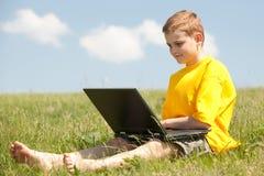 Slimme jongen met laptop op het gras Royalty-vrije Stock Foto