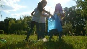 Slimme kleine milieudeskundigen die plastic flessen in vuilniszakken zetten stock footage