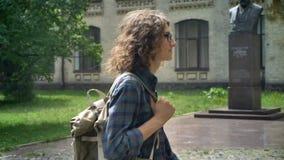 Slimme knappe student met krullend lang haar die aan universiteit lopen en rugzak houden, die schot bewegen, die in park dichtbij stock footage