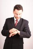 Slimme knappe zakenman die tijd controleert stock foto