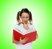 Slimme leuke meisjeslezing van een rood boek royalty-vrije stock afbeelding