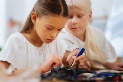 Slimme meisjes die een apparaat in een klaslokaal uitvinden royalty-vrije stock afbeeldingen