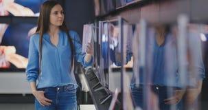 Slimme moderne vrouwelijke klant die grote Televisies kiezen bij elektronikaopslag Nieuwe het schermgeneraties stock video