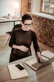Slimme professionele vrouw die laptop in het bureau met behulp van royalty-vrije stock foto's