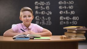 Slimme schooljongen die aan camera na het oplossen van taak, erachter geschreven oefeningen glimlachen stock videobeelden