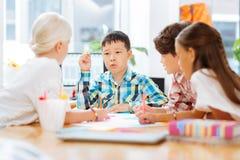 Slimme schooljongen die een verhaal vertellen aan zijn klasgenoten stock afbeelding