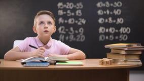 Slimme schooljongen die taak, wiskundeoefeningen oplossen die op bord erachter worden geschreven stock footage