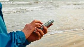 Slimme telefoon die bij oceaanstrand worden gebruikt stock videobeelden