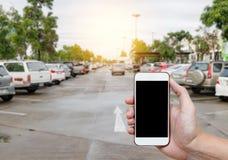Slimme telefoon die het lege scherm in mensenhand tonen met onduidelijk beeldparkeerterrein Royalty-vrije Stock Afbeelding