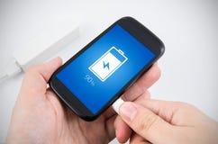 Slimme telefoon die met machtsbank belasten Stock Foto's