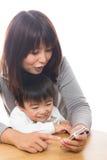 Slimme telefoon en ouder en kind Stock Foto's